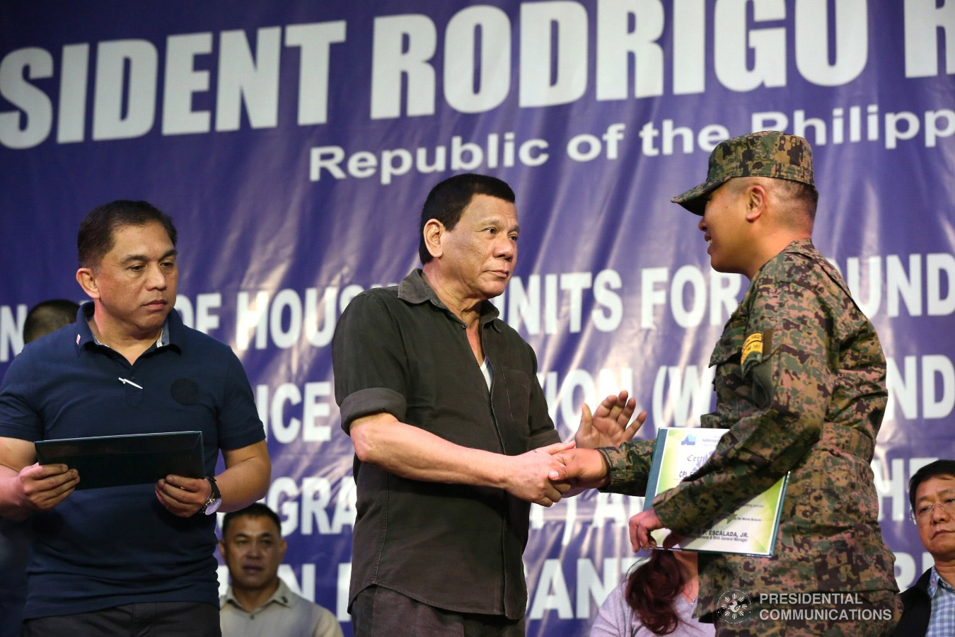 President Rodrigo Roa Duterte hands over a certificate of ownership to a wounded soldier who is one of the beneficiaries during the ceremonial turnover of housing units at the Pleasant View Residences in the City of San Jose del Monte, Bulacan on January 10, 2019. TOTO LOZANO/PRESIDENTIAL PHOTO