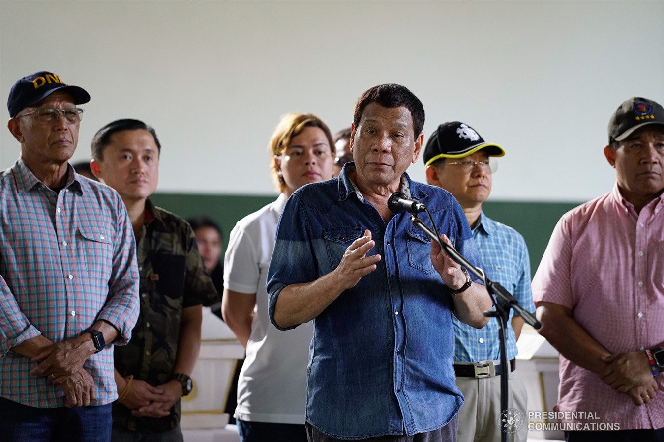 """President Rodrigo Roa Duterte offers his condolences to the families of the victims who died during the twin bombings at the Cathedral of Our Lady of Mount Carmel in Jolo, Sulu as he visited Camp Teodulfo Bautista in Jolo on January 28, 2019. Also in the photo are Defense Secretary Delfin Lorenzana, Former Special Assistant to the President Christopher Lawrence """"Bong"""" Go, Davao City Mayor Sara Duterte-Carpio, Interior and Local Government Secretary Eduardo Año, and National Security Adviser Hermogenes Esperon Jr. KING RODRIGUEZ/PRESIDENTIAL PHOTO"""