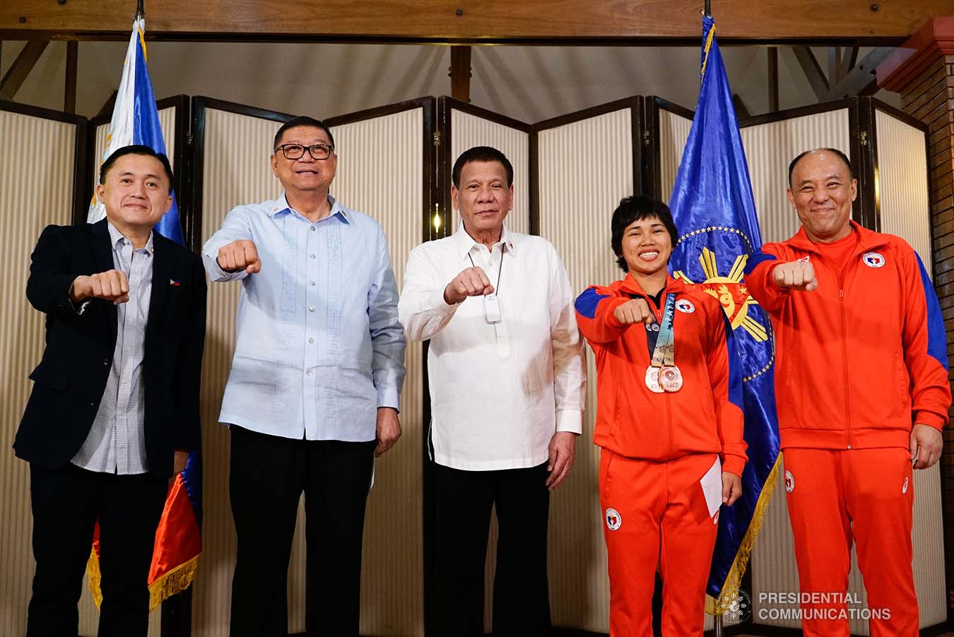 """President Rodrigo Roa Duterte strikes his signature pose with 2019 Asian Weightlifting Championships China Silver Medalist Hidilyn Diaz during their meeting at the Malago Clubhouse in Malacañang on October 16, 2019. Also in the photo are Senate Committee on Sports Chair Senator Christopher """"Bong"""" Go and Philippine Sports Commission Chairman William Ramirez. KING RODRIGUEZ/PRESIDENTIAL PHOTO"""