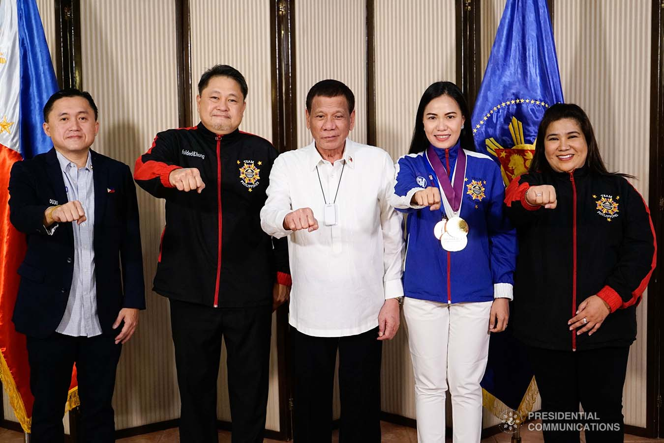 """President Rodrigo Roa Duterte strikes his signature pose with World Championships of Performing Arts (WCOPA) medalist Joanna Miranda during their meeting at the Malago Clubhouse in Malacañang on October 16, 2019. Also in the photo are Senate Committee on Sports Chair Senator Christopher """"Bong"""" Go, WCOPA National Director Gerardo Mercado, and Mary Mercado. KING RODRIGUEZ/PRESIDENTIAL PHOTO"""