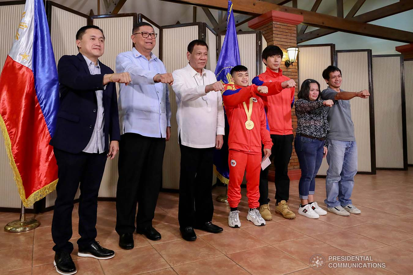 """President Rodrigo Roa Duterte strikes his signature pose with 49th FIG Artistic Gymnastics World Championships Gold Medalist Carlos Yulo during their meeting at the Malago Clubhouse in Malacañang on October 16, 2019. Also in the photo are Senate Committee on Sports Chair Senator Christopher """"Bong"""" Go and Philippine Sports Commission Chairman William Ramirez. RICHARD MADELO/PRESIDENTIAL PHOTO"""