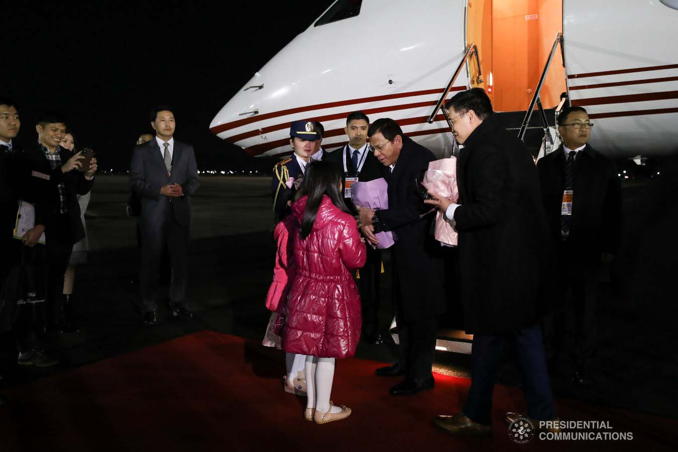 President Rodrigo Roa Duterte receives a token from the children who are part of the reception party upon his arrival at the Gimhae Air Base in Busan, Republic of Korea on November 25, 2019. KARL NORMAN ALONZO/PRESIDENTIAL PHOTO
