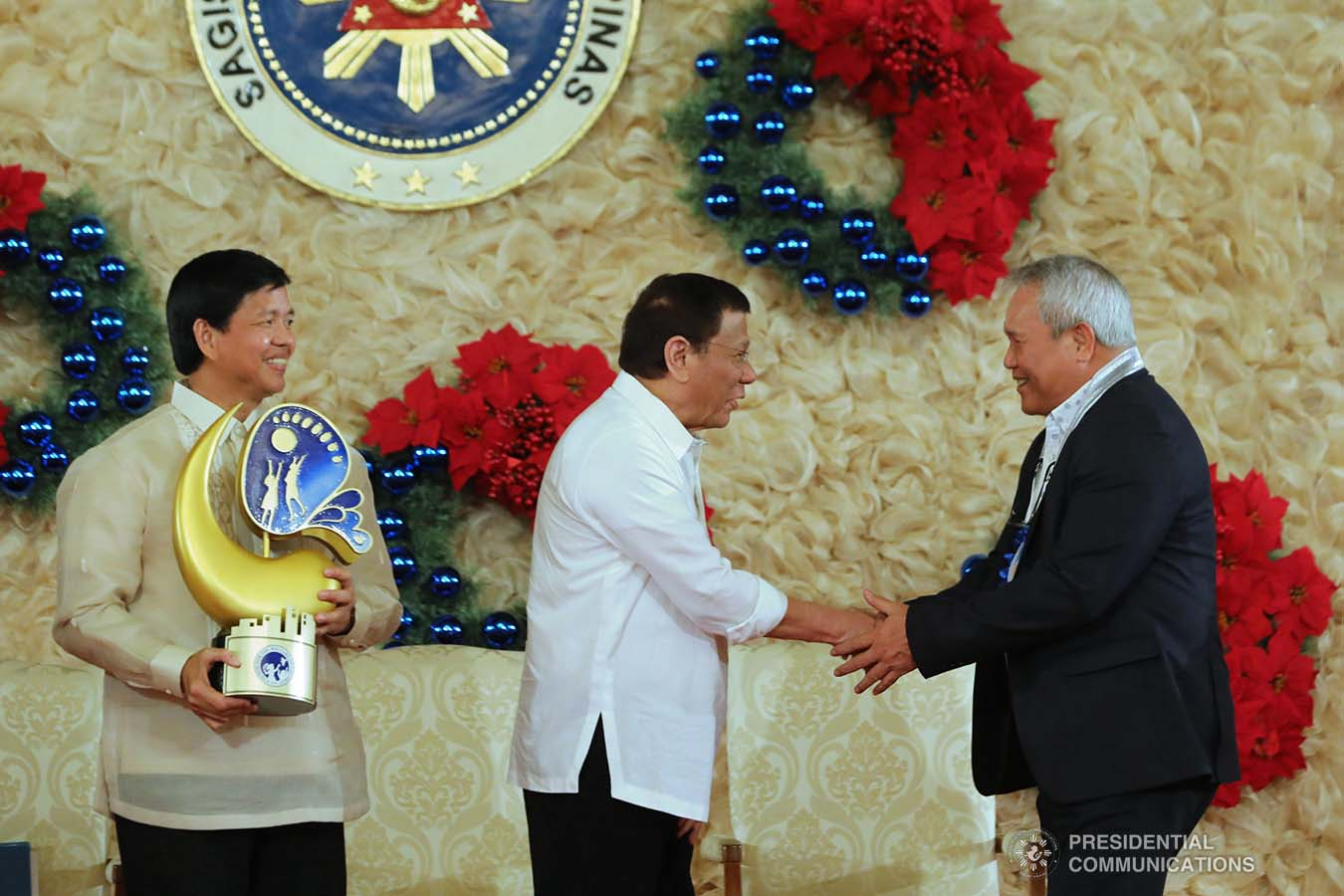President Rodrigo Roa Duterte congratulates one of the awardees of the 2018 Presidential Award for Child-Friendly Municipalities and Cities (PACFMC) during the awarding ceremony at the Malacañan Palace on November 28, 2019. Assisting the President is Social Welfare and Development Secretary Rolando Bautista. VALERIE ESCALERA/PRESIDENTIAL PHOTO