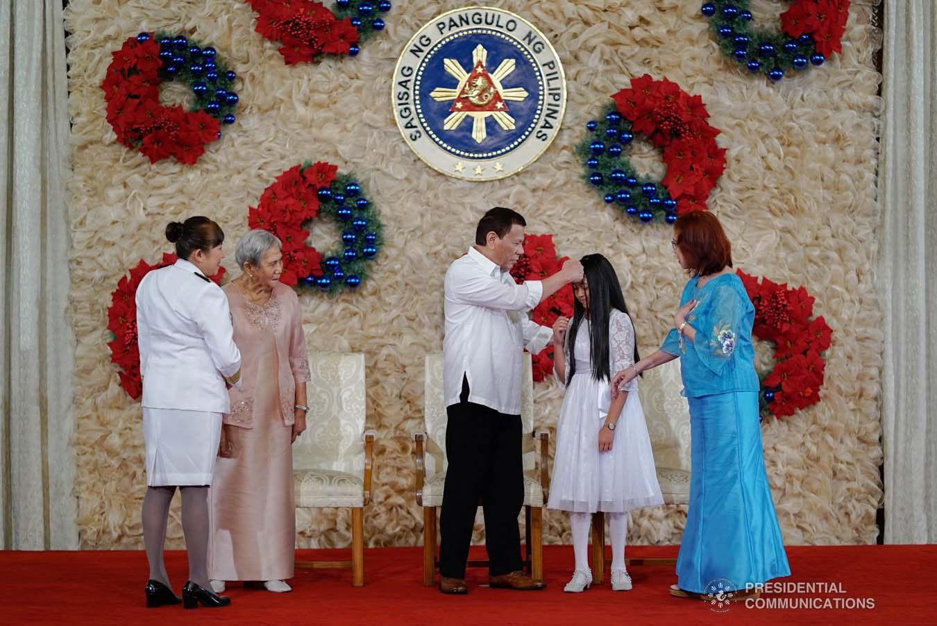 President Rodrigo Roa Duterte extends his hand to the daughter of newly promoted Fire Chief Superintendent Maria Mendoza who showed a gesture of respect to the President during the oath-taking ceremony at the Malacañan Palace on December 10, 2019. KING RODRIGUEZ/PRESIDENTIAL PHOTO