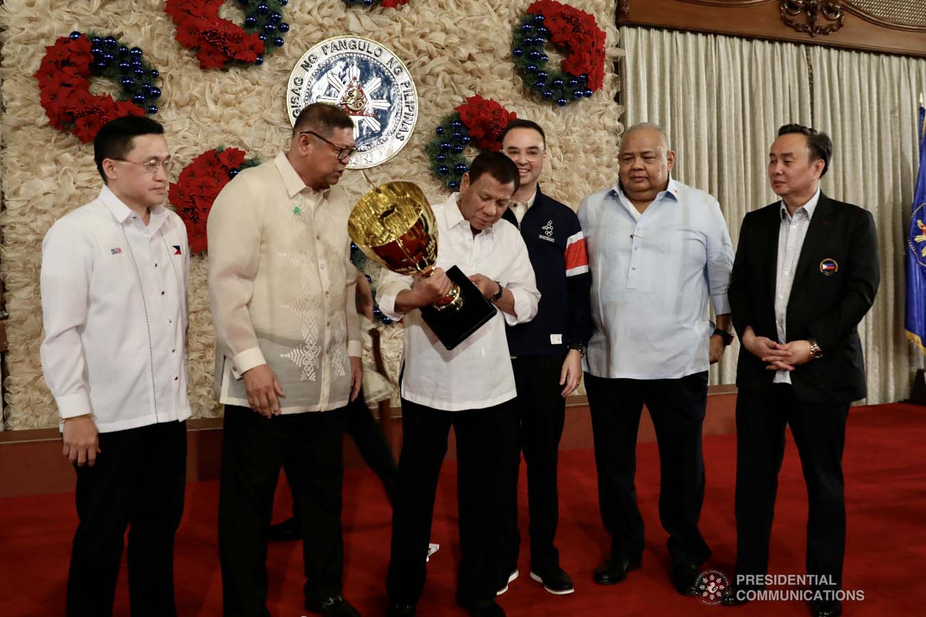 """President Rodrigo Roa Duterte holds the overall champion trophy of the Philippine Team during the recognition of the 2019 Southeast Asian Games medalists at the Malacañan Palace on December 18, 2019. The Philippine Team emerged as overall champion in the recently-concluded 2019 SEA Games after garnering 149 golds, 117 silvers and 121 bronzes. With the President are Senator Christopher """"Bong"""" Go, Philippine Sports Commission Chairman William Ramirez, Senator Alan Peter Cayetano, Executive Secretary Salvador Medialdea and Philippine Olympic Committee President and Cavite Eighth District Representative Abraham Tolentino. RICHARD MADELO/PRESIDENTIAL PHOTO"""
