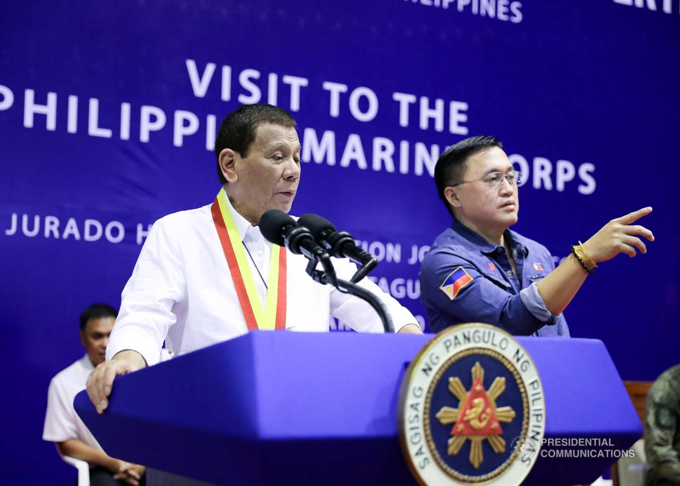 """President Rodrigo Roa Duterte confers with Senator Christopher """"Bong"""" Go while delivering a speech during his visit to the Philippine Marine Corps headquarters at Fort Bonifacio in Taguig City on January 13, 2020. ALFRED FRIAS/PRESIDENTIAL PHOTO"""