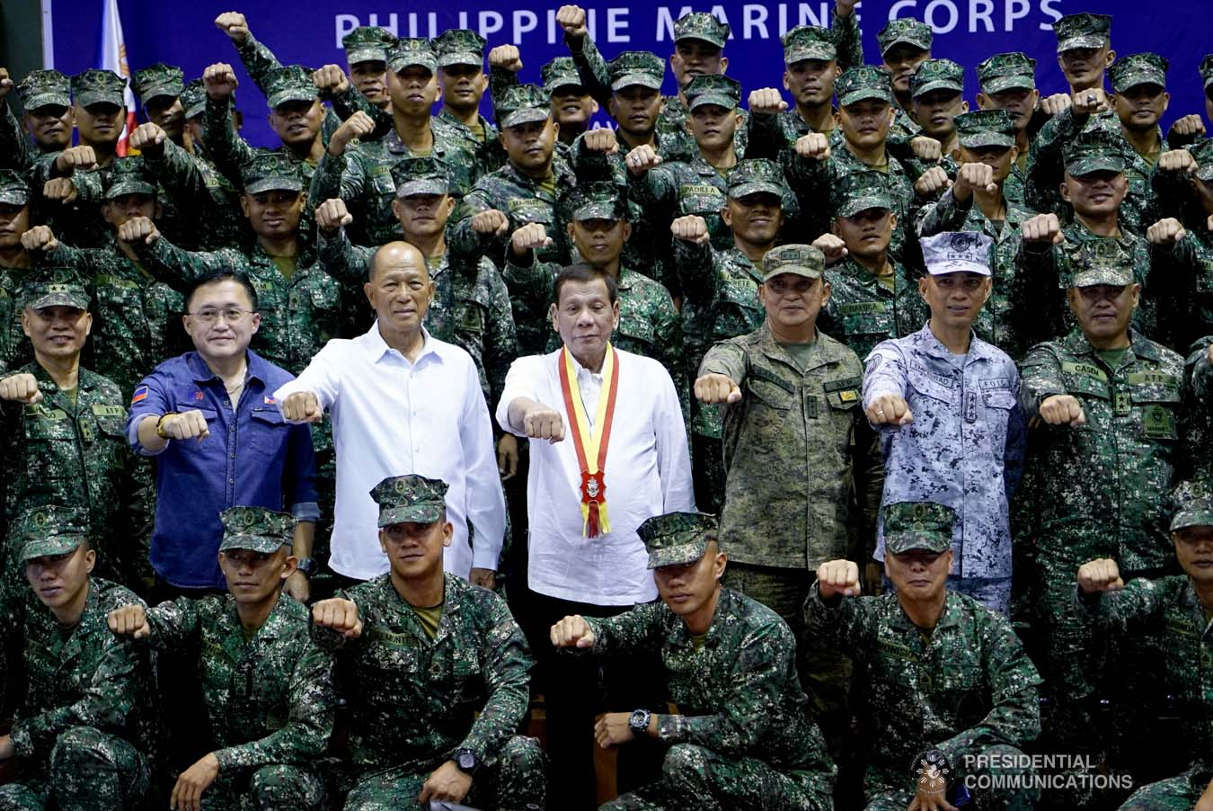 """President Rodrigo Roa Duterte strikes his signature pose with Senator Christopher """"Bong"""" Go, Defense Secretary Delfin Lorenzana and the officers and personnel of the Philippine Marine Corps during his visit at Fort Bonifacio in Taguig City on January 13, 2020. KING RODRIGUEZ/PRESIDENTIAL PHOTO"""
