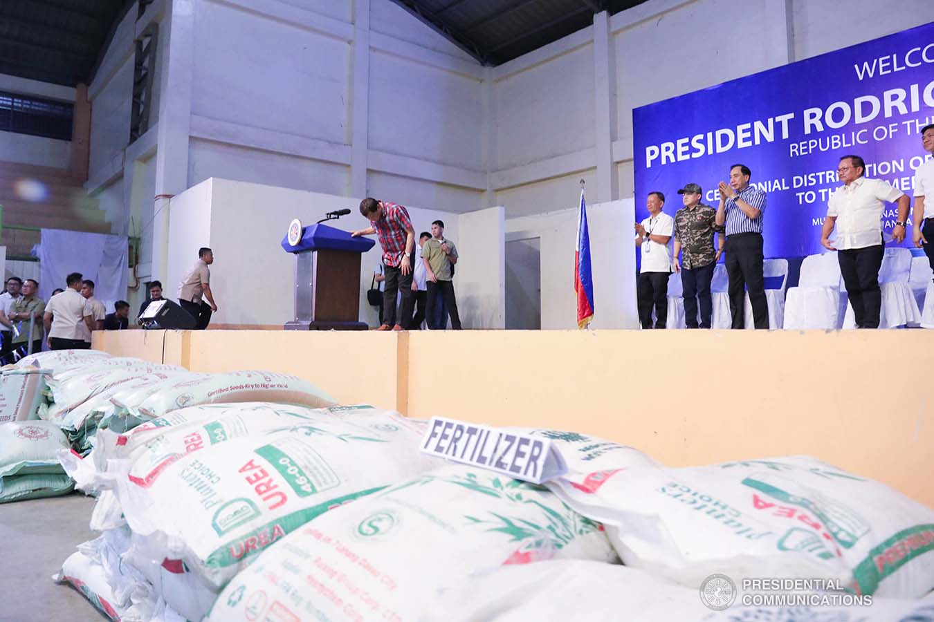 """President Rodrigo Roa Duterte takes a bow after delivering a speech during the ceremonial distribution of agricultural assistance to the farmers of Region 12 at the Pigcawayan Municipal Gymnasium in Cotabato on January 10, 2020. With the President are Senator Christopher """"Bong"""" Go and Agriculture Secretary William Dar. ROBINSON NIÑAL JR./PRESIDENTIAL PHOTO"""