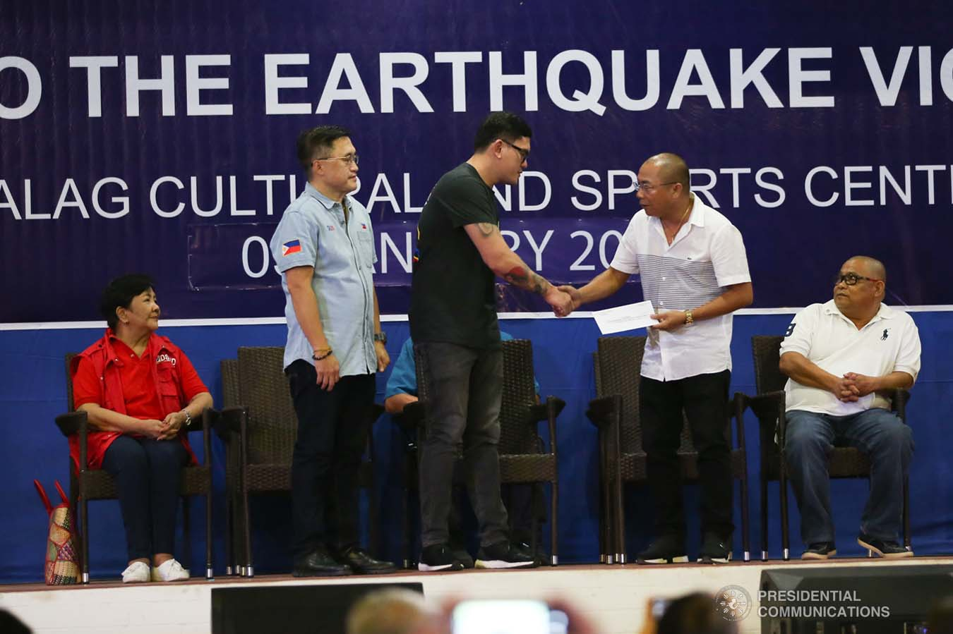 """Davao City Vice Mayor Sebastian Duterte, who visited earthquake victims in Malalag, Davao del Sur on behalf of his father President Rodrigo Roa Duterte, turns over a check worth P5 million to Malalag Mayor Peter Valentin during a ceremony at the Malalag Cultural and Sports Center on January 3, 2020. Assisting the President's son is Senator Christopher """"Bong"""" Go. KARL NORMAN ALONZO/PRESIDENTIAL PHOTO"""