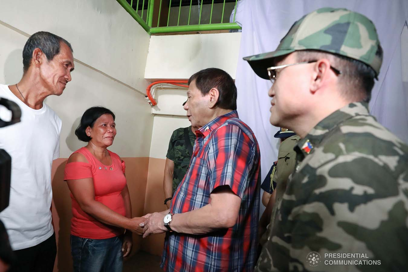 """President Rodrigo Roa Duterte chats with one of the recipients of agricultural assistance during the ceremonial distribution at the Pigcawayan Municipal Gymnasium in Cotabato on January 10, 2020. Also in photo is Senator Christopher """"Bong"""" Go. RICHARD MADELO/PRESIDENTIAL PHOTO"""