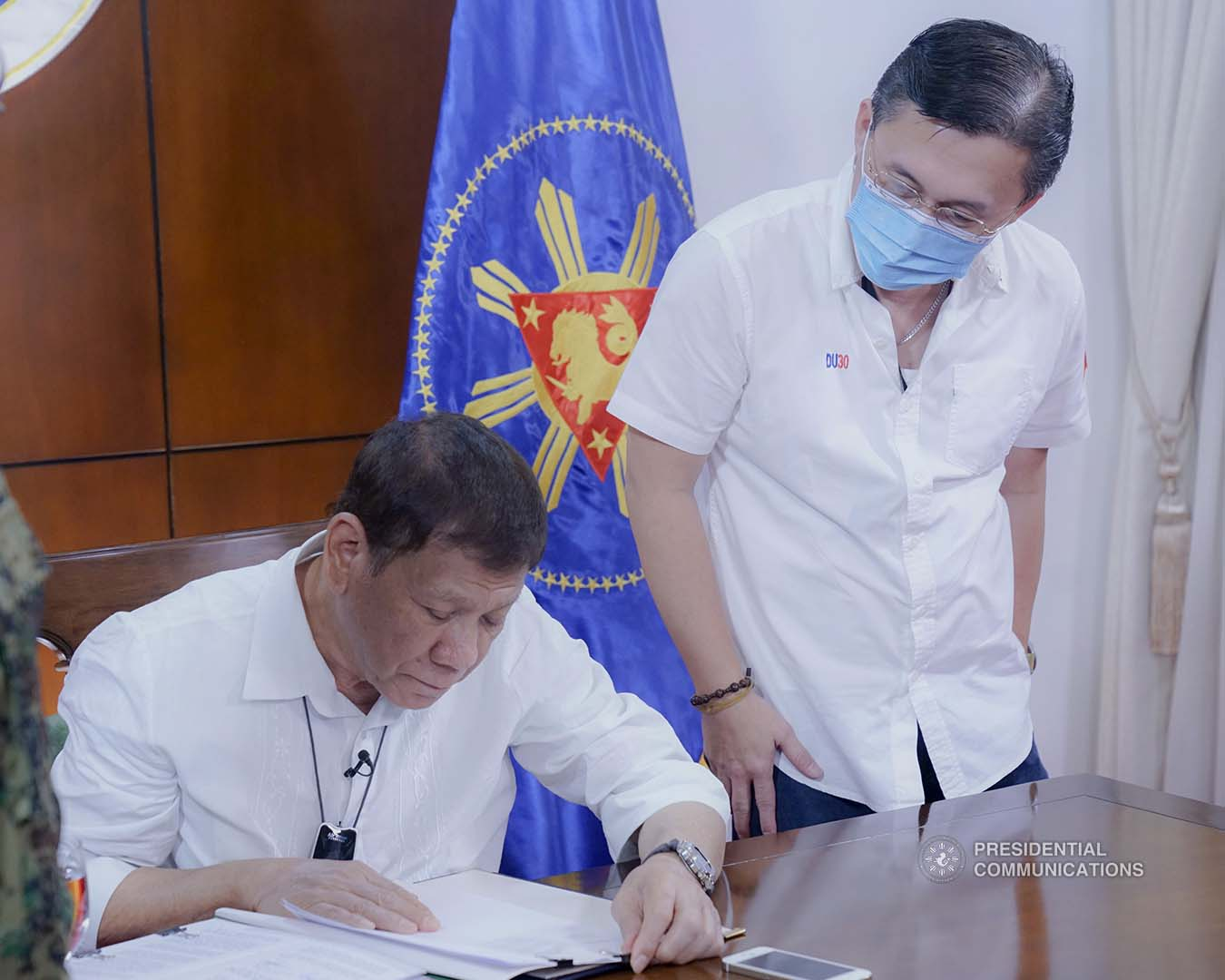 """President Rodrigo Roa Duterte signs into law the establishment of the National Academy of Sports during a ceremony at the Presidential Guest House in Panacan, Davao City on June 9, 2020. With the President is Senator Christopher """"Bong"""" Go. ARMAN BAYLON/PRESIDENTIAL PHOTO"""