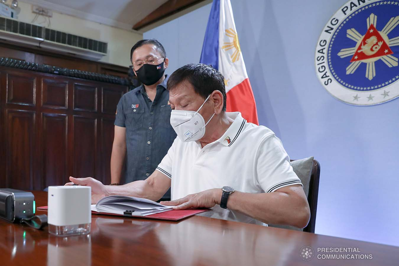 President Rodrigo Roa Duterte signs into law the Coronavirus Disease 2019 (COVID-19) Vaccination Program Act of 2021 at the Malacañang Golf (Malago) Clubhouse in Malacañang Park, Manila on February 26, 2021. The said law would expedite the procurement and administration of vaccines for the protection against COVID-19. It also covers the creation of an indemnity fund to cover compensation for those who would experience serious adverse effects to the vaccine. The President is accompanied by Senator Christopher Lawrence Go. KARL NORMAN ALONZO/ PRESIDENTIAL PHOTO